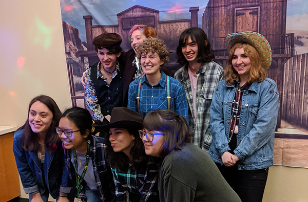 Members of the MCNH student club pose for a photo with western-themed backdrop